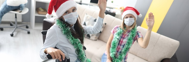 Disabled woman in wheelchair and friend in medical mask greeting christmas at home and waving