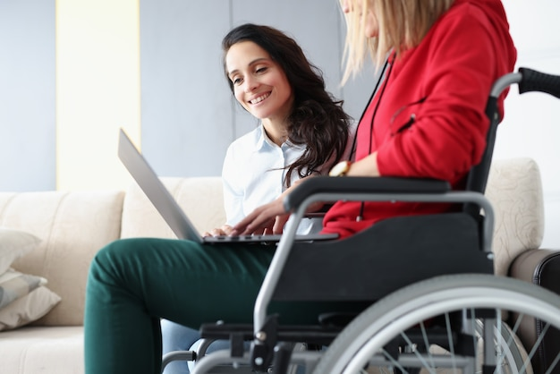 Disabled woman in wheelchair and her friend looking at laptop screen at home