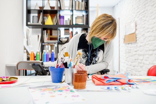 Disabled woman in a wheelchair learning to paint at a drawing academy