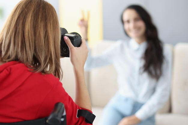 Disabled woman in wheelchair photographing girl closeup