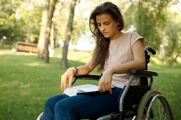 Disabled woman in wheelchair reading book in park