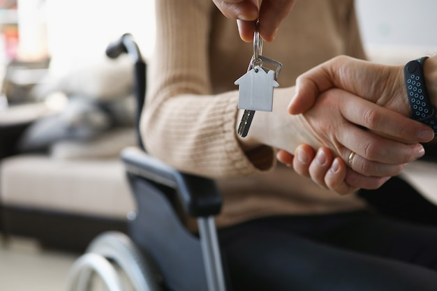 Disabled woman in wheelchair shaking hands with man with keys to new apartment closeup