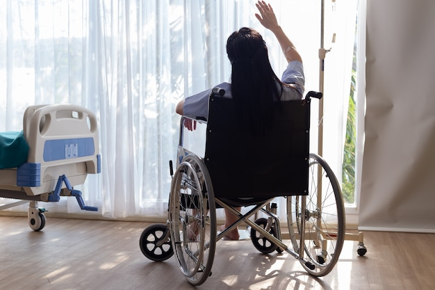 Disabled woman in a wheelchair sits of window in patient room.