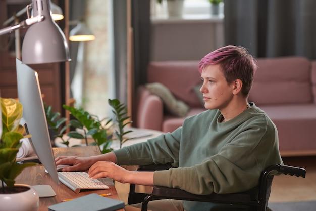 コンピューターの前のテーブルに座って、自宅でオンラインで作業している短い髪の障害のある女性
