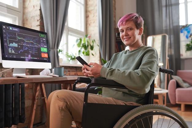 車椅子に座って、自宅のコンピューターでの作業中に携帯電話でオンラインで作業している短い髪の障害のある女性