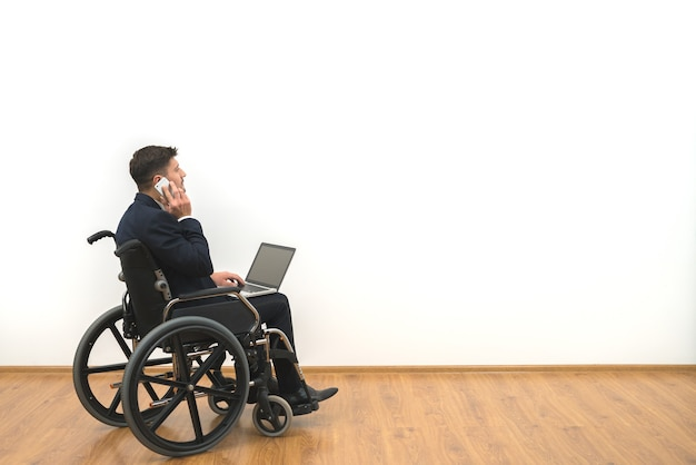The disabled working with a laptop and phone on the white wall background