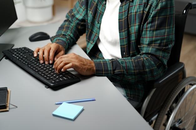 Молодой афроамериканец-инвалид в инвалидной коляске с помощью компьютера, сидя за своим рабочим столом