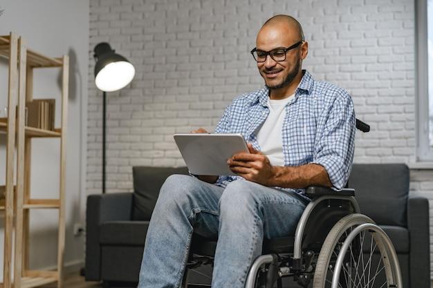 휠체어에 앉아 디지털 태블릿을 사용하는 장애인 젊은 아프리카계 미국인 남자