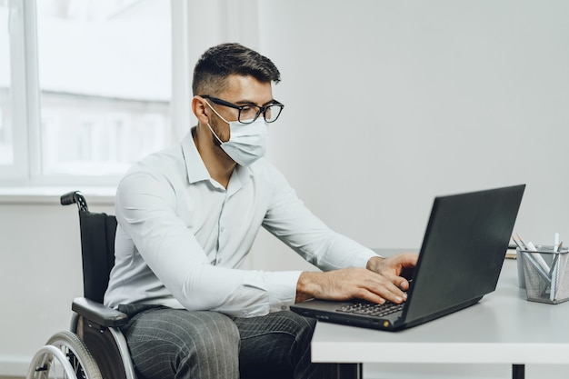 Disabled young businessman doing his job and wearing medical face mask