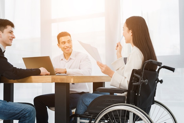 Disabled young businesswoman sitting on wheelchair discussing with his male colleague in office