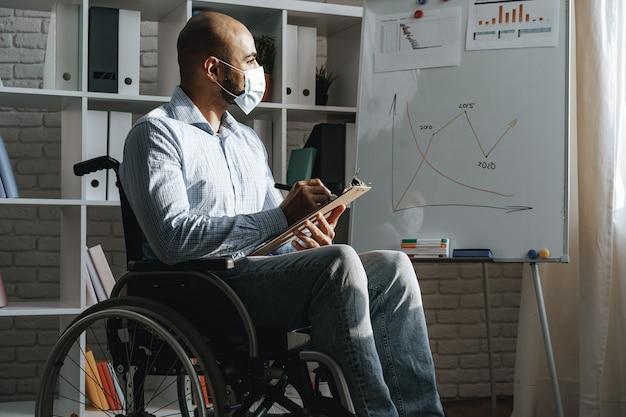 Молодой человек-инвалид делает презентацию в офисе в медицинской маске