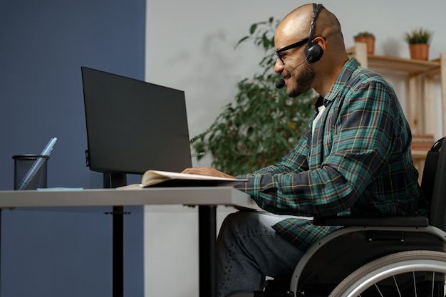 Disabled young man in wheelchair working at his working table with headset on