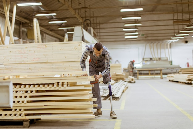 Disabled young man with an artificial leg is working at the furniture  factory