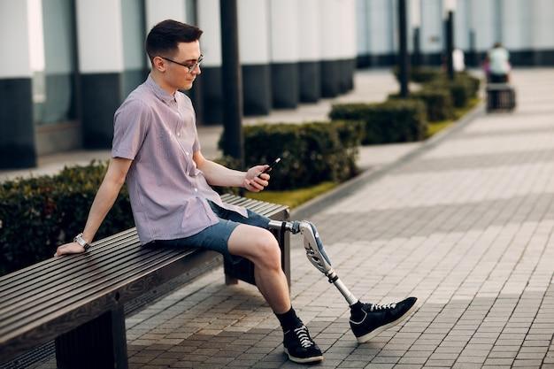 Молодой человек-инвалид с протезом стопы сидит на скамейке на городской улице и держит мобильный телефон на открытом воздухе
