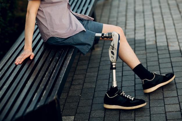 屋外に座っている義足と無効になっている若い男