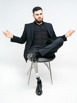 Неработающий молодой человек при протезная нога сидя на стуле в студии над белой стеной, концепцией протеза