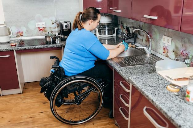 特別装備のキッチンで皿を洗う車椅子の若い女性を無効に
