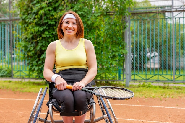 Disabled young woman on wheelchair playing tennis on tennis court.