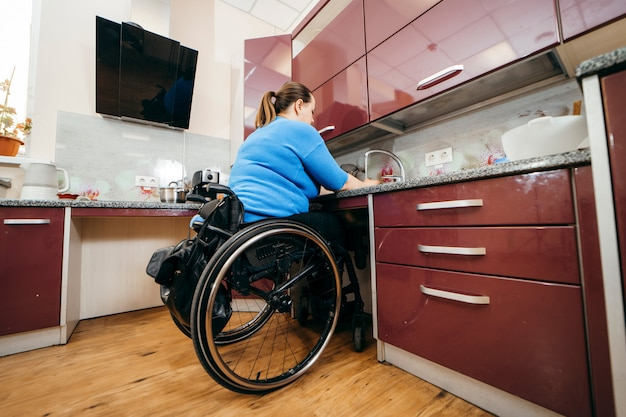 Disabled young woman in wheelchair washing dishes in specially equipped kitchen
