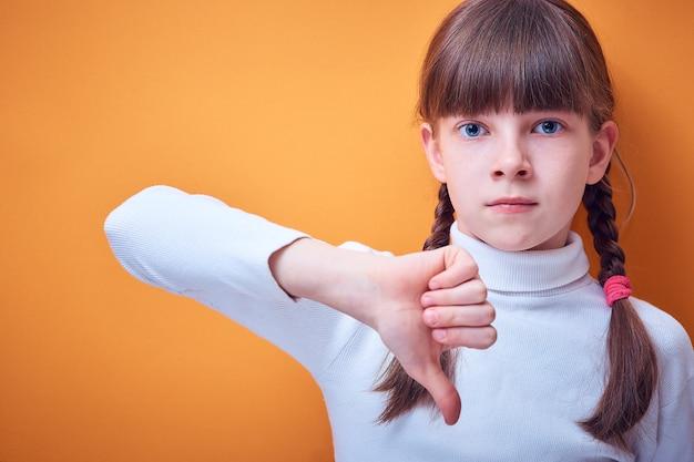 意見の相違と抗議、白人の十代の少女は色付きで親指を下に表示します