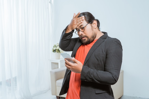 Disapointed businessman receiving text message on his smartphone