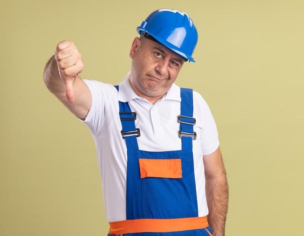Uomo adulto deluso del costruttore in pollici uniformi verso il basso isolati sulla parete verde oliva