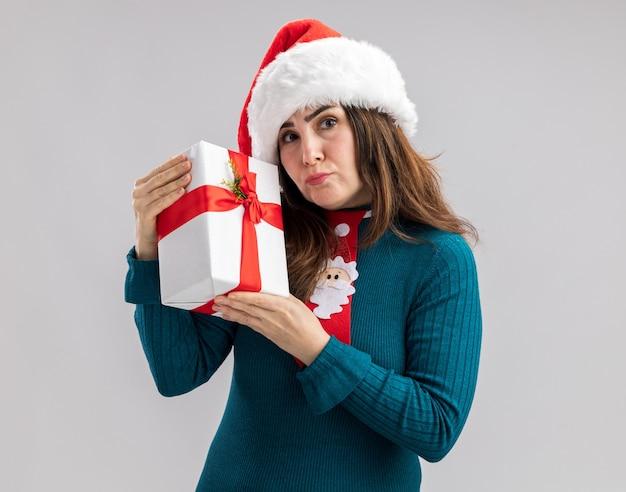 コピースペースと白い背景で隔離のクリスマスギフトボックスを保持しているサンタ帽子とサンタネクタイと失望した大人の白人女性
