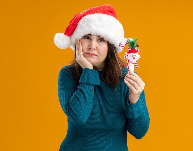 La donna caucasica adulta delusa con il cappello della santa mette la mano sul mento e tiene il bastoncino di zucchero isolato su fondo arancio con lo spazio della copia