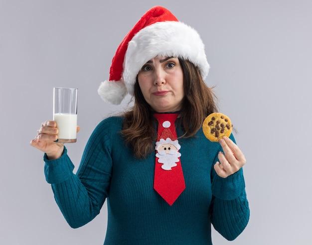 Donna indoeuropea adulta delusa con santa cappello e cravatta santa tenendo un bicchiere di latte e cookie isolato su sfondo bianco con spazio di copia