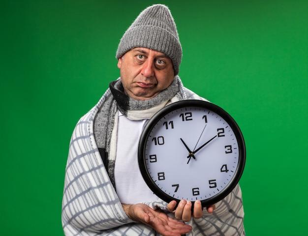 Deluso adulto malato uomo caucasico con sciarpa intorno al collo indossando cappello invernale avvolto in plaid tenendo l'orologio isolato sulla parete verde con spazio di copia