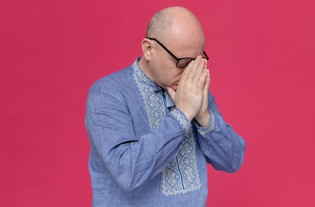 Uomo adulto deluso in camicia blu con gli occhiali che si mette le mani sul naso