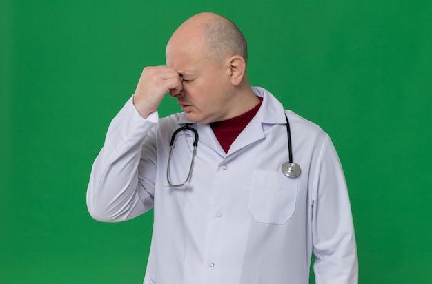 Uomo adulto deluso in uniforme da medico con stetoscopio che si tiene il naso