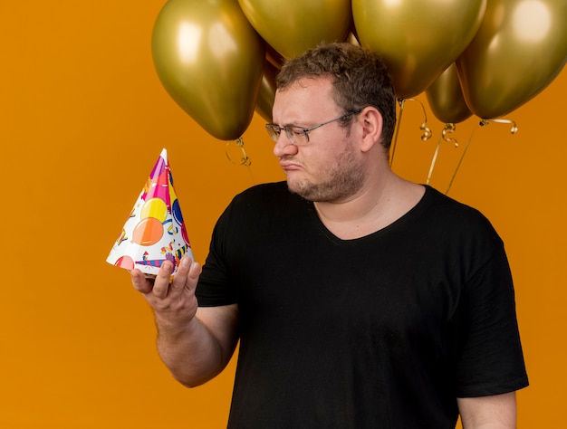 광학 안경에 실망한 성인 슬라브 남자가 헬륨 풍선 앞에 서 생일 모자를 들고보고