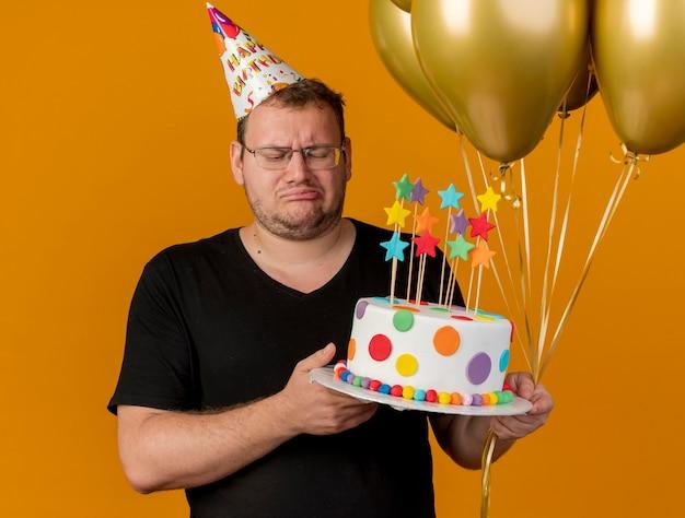 생일 모자를 쓰고 광학 안경에 실망한 성인 슬라브 남자가 헬륨 풍선과 생일 케이크를 보유하고 있습니다.