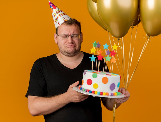 Disappointed adult slavic man in optical glasses wearing birthday cap holds helium balloons and birthday cake