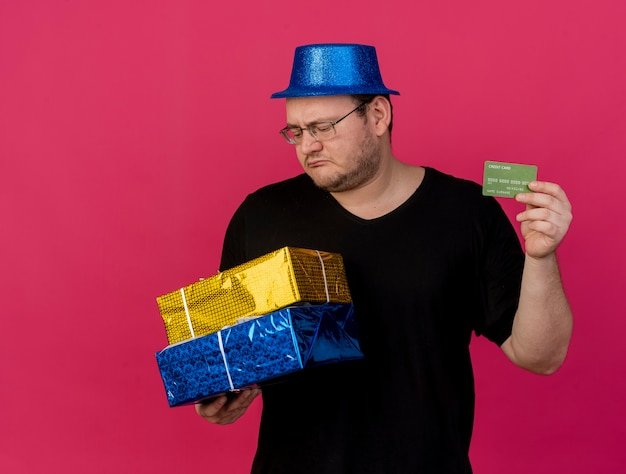 Disappointed adult slavic man in optical glasses wearing blue party hat holds gift boxes and credit card