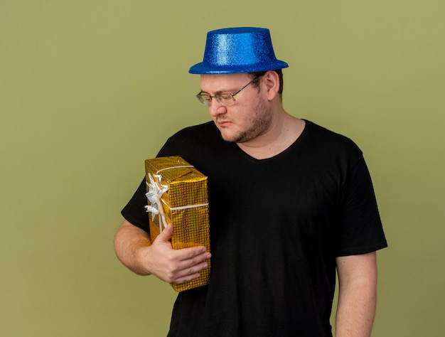 Disappointed adult slavic man in optical glasses wearing blue party hat holds and looks at gift box