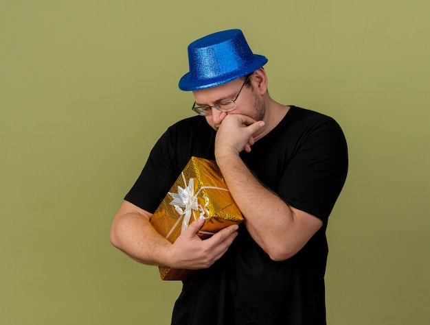 Disappointed adult slavic man in optical glasses wearing blue party hat puts hand on chin holds gift box