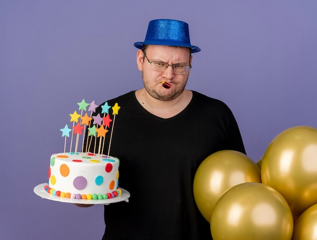 Disappointed adult slavic man in optical glasses wearing blue party hat stands with helium balloons holding birthday cake and blowing party whistle