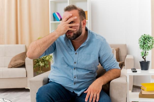 실망한 성인 슬라브 남자는 거실 내부의 손가락을 통해 카메라를보고 얼굴에 손을 넣어 안락 의자에 앉아