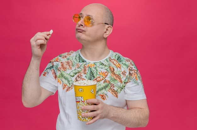 Разочарованный взрослый славянский мужчина в солнцезащитных очках держит ведро попкорна и смотрит вверх