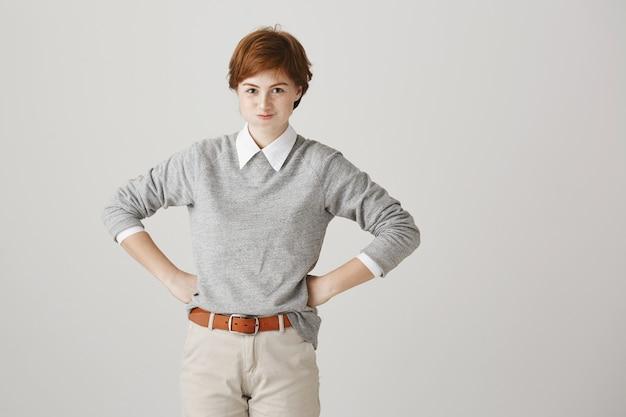 Разочарованная и раздраженная рыжая девушка с короткой стрижкой позирует у белой стены