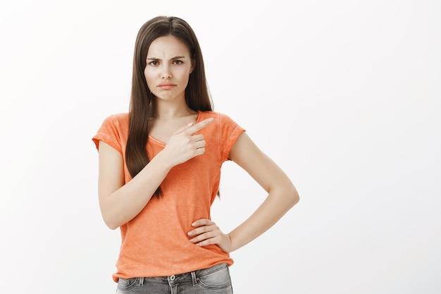 실망하고 불평하는 귀여운 찡그린 소녀는 프로모션을 좋아하지 않고 오른쪽 상단 모서리를 가리키며 불쾌감을 느낍니다.