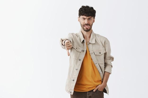 Разочарованный и жалующийся стильный бородатый парень позирует на фоне белой стены