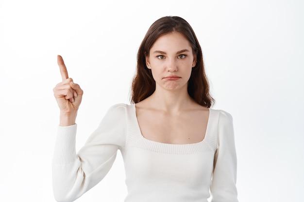 불공평한 나쁜 일을 가리키는 실망스럽고 슬픈 소녀, 상단의 로고를 가리키고 화가 난 삐죽삐죽, 흰 벽에 불만스럽게 서 있는