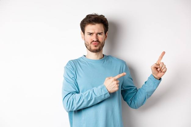 실망 하 고 화가 젊은 남자 나쁜 제안을 보여주는, 오른쪽 손가락을 가리키고 흰색 배경에 회의적인 얼굴로 서 역겨운 인상을 찌 푸 리고.
