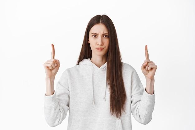 失望して動揺している若い女性が指を上に向け、判断と疑いを持って見て、眉をひそめ、不機嫌にふくれっ面