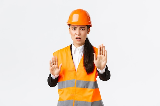 Disappointed angry asian female engineer in safety helmet and reflective clothing saying stop, prohibit and disagree with construction manager, showing enough, no gesture, white wall.