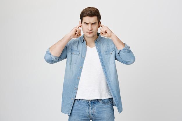 Разочарованный злой парень заткнул уши от шума
