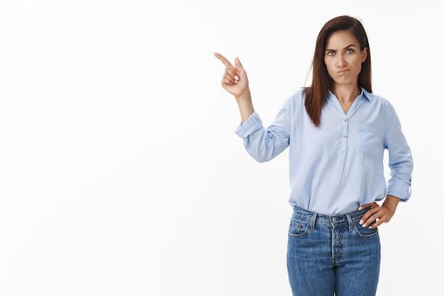 문신을 한 팔을 가진 화난 진지한 백인 여성, 참을성 없는 웃음, 당황한 왼쪽 삐죽을 가리키는 딸, 꾸짖는 딸, 옆으로 카피스페이스 표시, 흰 벽